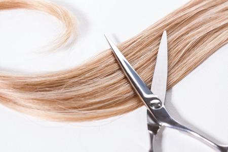 peluqueria: Bloqueo de pelo castaño con las tijeras en un fondo blanco en un concepto de peluquería y peinados