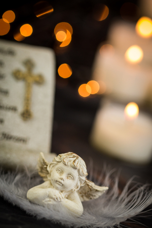 lit image: Religious Themed Christmas Image with Prayer and Angel Statue in front of Lit Candles on Dark Background with Twinkling Lights