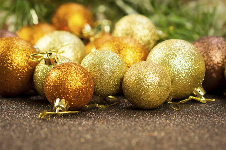 shiny christmas baubles: Golden Christmas bauble background with selective focus to a single glitter ball in the foreground with a blurred pile behind giving a warm ambiance and copyspace for your seasonal greeting