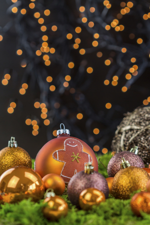 hued: Still Life of Orange Hued Festive Christmas Balls in Variety of Textures and Surfaces with Gingerbread Baking Theme on Dark Background Illuminated by Twinkling Lights