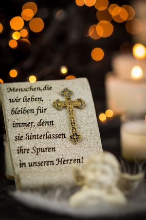 vigil: Religious Themed Christmas Image with Prayer and Angel Statue in front of Lit Candles on Dark Background with Twinkling Lights