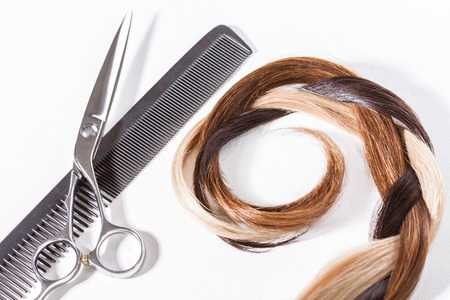 auburn hair: Lock of auburn hair with scissors on a white background in a concept of hairdressing and hairstyling