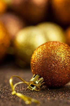 ambiance: Golden Christmas bauble background with selective focus to a single glitter ball in the foreground with a blurred pile behind giving a warm ambiance and copyspace Stock Photo