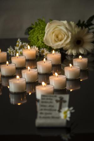 feier: Trauerkarte und Gedenkkerzenlicht auf schwarzem Hintergrund