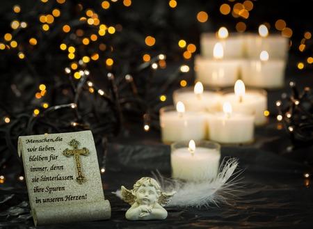 Godsdienstige Kerstmis Themed afbeelding met Gebed en Angel Standbeeld voor Lit kaarsen op donkere achtergrond met Twinkling Lights