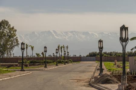 topografia: Paisaje de invierno en Marrakech, Marruecos con la revista Rolling colinas cubiertas de hierba verde y viviendas rurales apoyados por una cadena de montañas cubiertas de nieve en la distancia que muestra la topografía del país