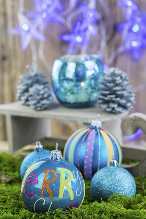 candleholder: Decorative blue Christmas background with patterned baubles , blue pine cones, candleholder and star shaped party lights in cool winter tones