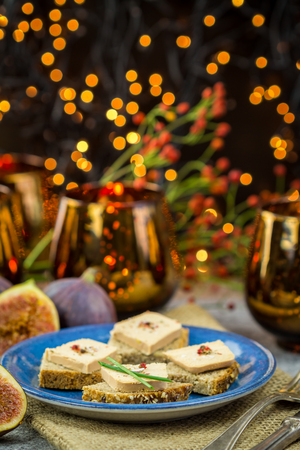 Foie gras on wholewheat bread with juicy ripe figs served as snacks at a festive celebration with colorful party lights in the background Imagens