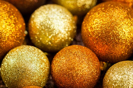 ambiance: Golden Christmas bauble background with selective focus to a single glitter ball in the foreground with a blurred pile behind giving a warm ambiance and copyspace for your seasonal greeting