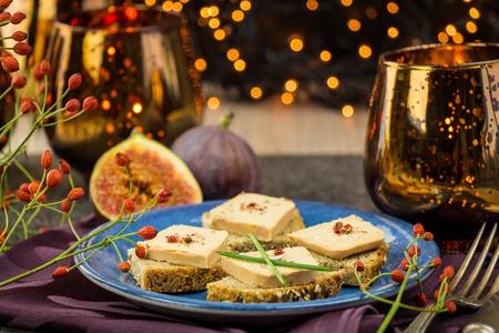 comida de navidad: Foie gras de pan integral con higos maduros jugosos sirvió como aperitivos en una celebración festiva con luces de fiesta de colores en el fondo