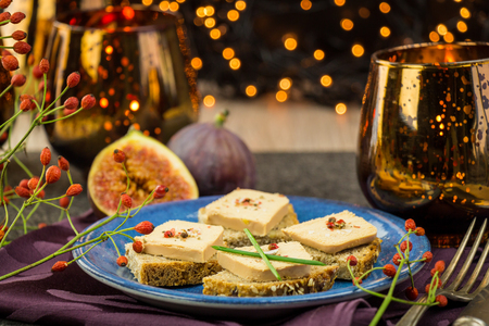 christmas party: Foie gras on wholewheat bread with juicy ripe figs served as snacks at a festive celebration with colorful party lights in the background Stock Photo