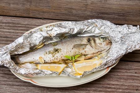 peces: Vista elevada de pescado fresco preparado con hierbas y cu�as de lim�n al vapor en hoja de lata de paquetes y servidos en bandeja en mesa de madera r�stica Foto de archivo