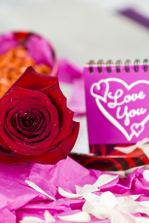courting: Romantic gift of bonbons in a heart shaped box opened to show the contents on pink wrapping paper and decorated with a red rose for Love and card with text - Love You - on Valentines Day Stock Photo