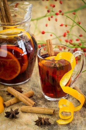 star anise christmas: Delicious spicy hot mulled red wine with cinnamon, star anise and orange peel served in a carafe and glass for a cold winter evening or festive Christmas beverage