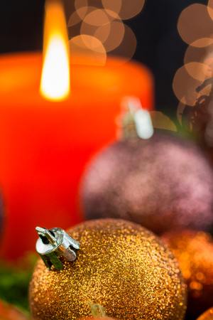 advent candles: Burning red advent candle with brown and coppery themed Christmas baubles and a sparkling bokeh of party lights in the background for a festive seasonal celebration Stock Photo