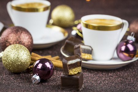 half ball: Festive Still Life of Half Eaten Christmas Confectionery and Ball Decorations in front of Two Coffee Cups with Golden Rims in Blurred Background with Twinkling Strings of Lights