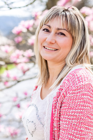 woman middle age: Waist Up Portrait of Smiling Mature Woman Wearing Pink Sweater Outdoors on Spring Day with Magnolia Tree in Bloom in Background Stock Photo