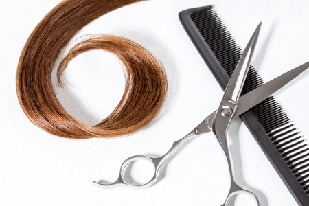 Lock of straight hair in curl with scissors and comb