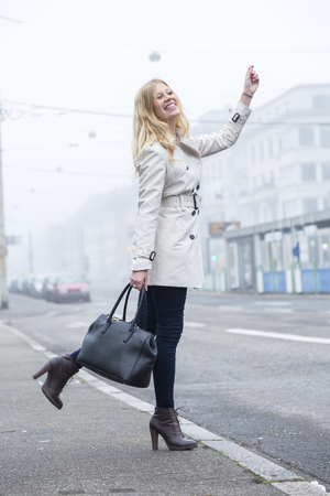 Attractive trendy young woman in high heels standing at the edge of an urban street hailing a taxi cab with a smile while balancing on one leg