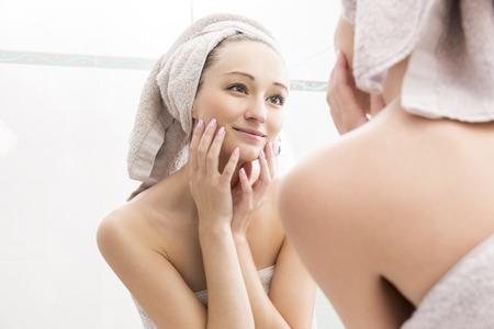 espejo: Retrato de la mujer joven en la reflexi�n de la persona en Espejo de ba�o - Joven mujer envuelta en toallas despu�s de la ducha y en la cara tocando con la mano y mir�ndose en un espejo
