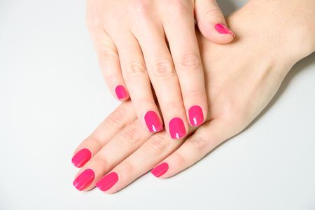 コピー スペース - マニキュアの詳細と明白で白い面に折り畳まれた手の爪に明るいピンクのマニキュアを着て女性の高角クローズします。