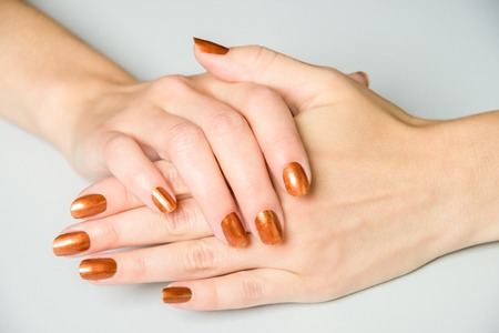 splayed: Pair of open female hands with brown metallic paint on fingernails resting on white background Stock Photo