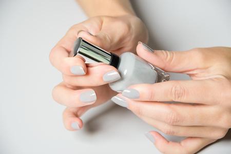 uñas pintadas: Un par de manos femeninas abren la botella de esmalte de uñas Foto de archivo