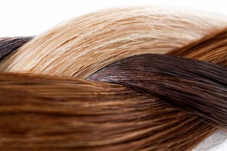 Blond, bruin en zwart haar geweven in een vlecht over wit