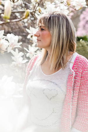 admiring: Obscured Waist Up of Mature Woman Wearing Pink Sweater Standing Outdoors on Sunny Spring Day Looking Up and Admiring Beauty of White Magnolia Blooms on Tree with Fog in Foreground