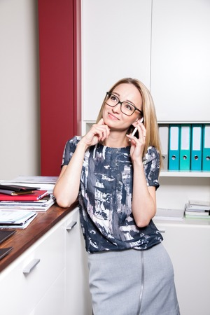 office cubicle: Waist Up Portrait of Smiling Young Blond Business Woman Standing in Office in Cubicle Wearing Patterned Top and Eyeglasses While Talking on Modern Slim Cell Phone Stock Photo
