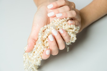 bunched: Close Up of Female Hands Wearing White Nail Polish and Cupping Long Strand of Pearls in Palms on Neutral Gray Surface with Copy Space Stock Photo