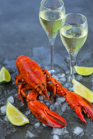 wine glasses: Fresh Lobster Chilling on Ice with Wedges of Lime and Two Glasses of Celebratory Sparkling Wine or Champagne - Still Life of Celebratory Lobster Dinner with Wine Stock Photo