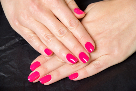 pink nail polish: Close Up of Woman with Manicure in Bright Pink - Detail of Female Hands Folded and Wearing Bright Pink Nail Polish on Dark Background Stock Photo