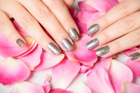 Close-up van de handen met metallic vingernagel verf over verspreid roze rozenblaadjes