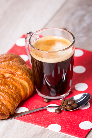 polka dotted: Delicious breakfast setting on gray wooden table with coffee in glass cup next to spoon and croissant on polka dotted napkin Stock Photo