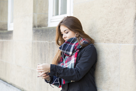tunes: Trendy attractive young girl listening to music on her mobile phone and earplugs sitting on urban steps checking the tunes in her library Stock Photo