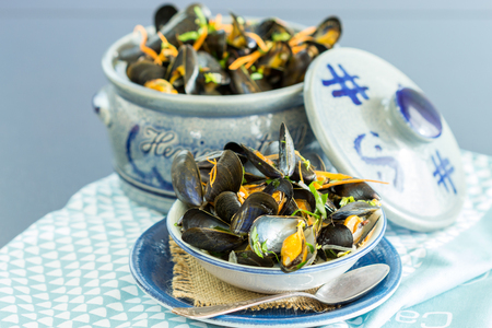 placemat: Close Up of Appetizing Fresh Mussels in Small Single Serving Bowl Positioned in front of Ceramic Serving Bowl and Served on Blue Table with Placemat