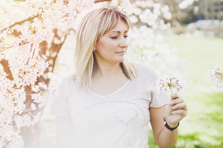 Obscured Waist Up of Mature Woman Wearing Pink Sweater Standing Outdoors on Sunny Spring Day Looking Up and Admiring Beauty of White Magnolia Blooms on Tree with Fog in Foreground