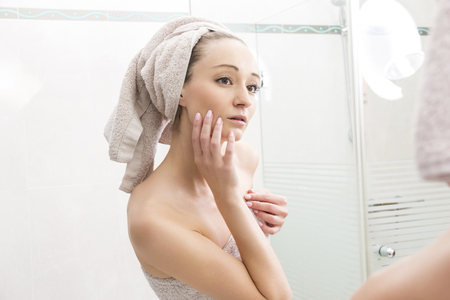 hair wrapped up: Portrait of Young Woman Smiling at Reflection of Self in Bathroom Mirror - Young Woman Wrapped in Towels After Shower and Touching Face with Hands and Looking at Self in Mirror
