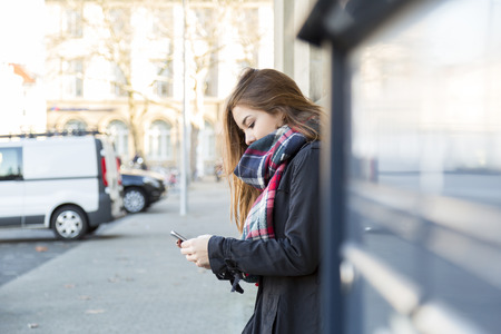 tune: Attractive young city girl listening to music on her mobile phone leaning against a commercial building as she selects a new tune from her library, with copy space