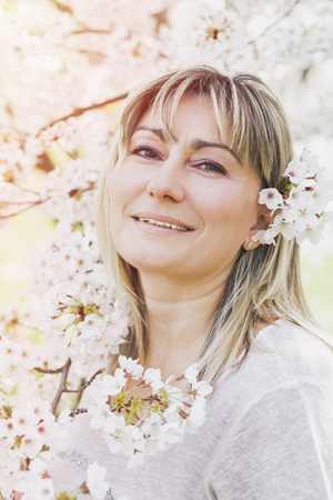 waist up: Obscured Waist Up of Mature Woman Wearing Pink Sweater Standing Outdoors on Sunny Spring Day Looking Up and Admiring Beauty of White Magnolia Blooms on Tree with Fog in Foreground