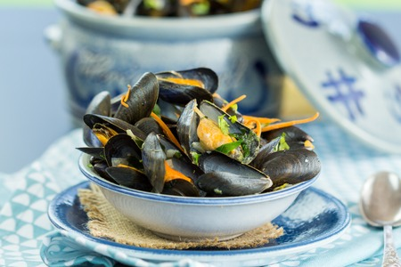 positioned: Close Up of Appetizing Fresh Mussels in Small Single Serving Bowl Positioned in front of Ceramic Serving Bowl and Served on Blue Table with Placemat