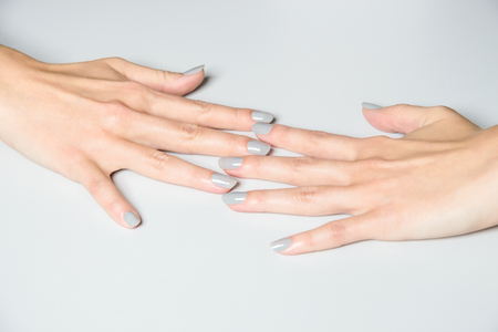 manicured hands: Pair of female manicured hands on white table