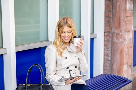e book device: Stylish attractive young woman sitting waiting for transport on a bench outdoors drinking coffee and reading information on her tablet computer