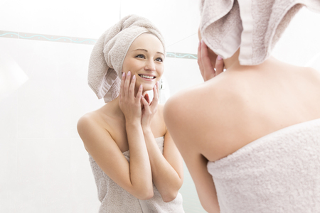 hand washing: Portrait of Young Woman Smiling at Reflection of Self in Bathroom Mirror - Young Woman Wrapped in Towels After Shower and Touching Face with Hands and Looking at Self in Mirror