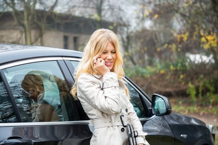 leans on hand: Vivacious stylish young blond woman chatting on a mobile phone as she leans back against a car with her tablet computer in her hand Stock Photo