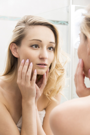 narcissistic: Head and Shoulders Close Up of Young Blond Woman Touching Face and Looking Approvingly at Reflection in Bathroom Mirror