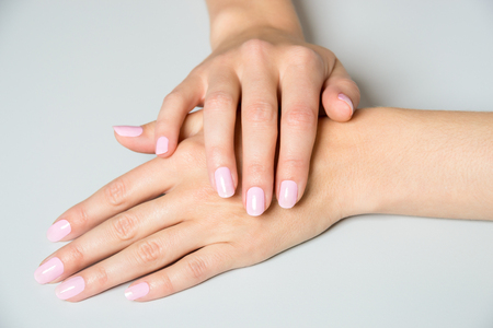Two female hands in elegant pose with pale pink painted nails on gray surface