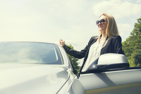 vivacious: Vivacious stylish young blond woman as she leans back against a car Stock Photo