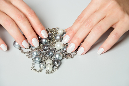 draped: Close Up of Female Hands Wearing White Nail Polish with Silver Chain Necklaces with Gray Pearls Draped Over Sides with Gray Background and Copy Space